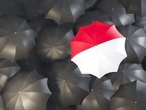 Umbrella with flag of monaco. On top of black umbrellas. 3D illustration Royalty Free Stock Photo