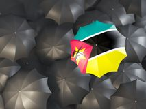 Umbrella with flag of mozambique. On top of black umbrellas. 3D illustration Stock Photos