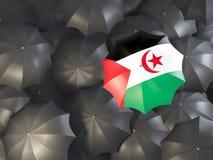 Umbrella with flag of western sahara. On top of black umbrellas. 3D illustration Stock Photos