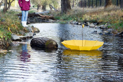 Umbrella floating away in wind on river. Bright yellow umbrella swims on the river in the wind in autumn Royalty Free Stock Photo
