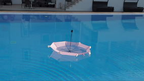 Umbrella floating in swimming pool stock footage