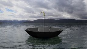 Umbrella floating on water, with distant mountains and cloudy sky Royalty Free Stock Images