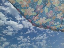 Umbrella with floral pattern. Under cloudy sky Stock Photography