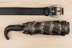 Umbrella and genuine leather strap lie on a wooden surface Royalty Free Stock Photography