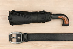 Umbrella and genuine leather strap lie on a wooden surface Stock Photo