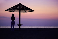 Umbrella and the girl on a beach. Evening Stock Images