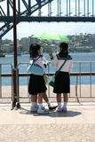 Umbrella girls. Three asiatic girls protected by umbrella near the water Royalty Free Stock Photography