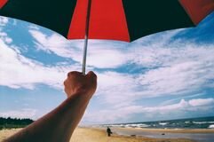 Umbrella in hand on a beach Stock Images