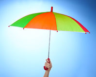 umbrella in hand on blue Royalty Free Stock Images