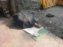 Umbrella house. An umbrella used as a house on the streets of Mumbai Stock Photo