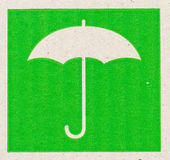 Umbrella image of fragile symbol on cardboard. Royalty Free Stock Photos