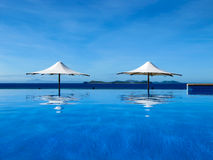 Umbrella between an infinity pool and the sea Royalty Free Stock Photo