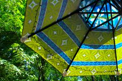 THE UMBRELLA. A large colorful umbrella in shades of blue and green has a backdrop of green, leafy trees. It is a unique photo of a common object royalty free stock image
