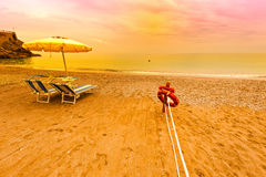 Umbrella and Lifebuoy. Beach Umbrella and Lifebuoy on the Sandy Coast at Sunrise stock image