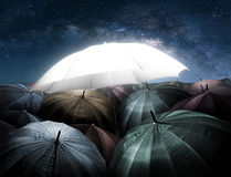 Umbrella lights glowing standing out from crowd of dark umbrella. Business, leadership concept, being different concepts royalty free stock photo