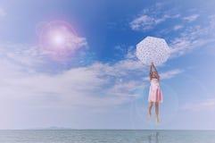 Umbrella little girl jumping on the sand Stock Image