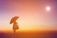 Umbrella little girl stand. And sunset silhouette Royalty Free Stock Images