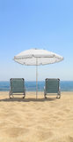Umbrella and lounge chairs on idyllic beach Royalty Free Stock Photos