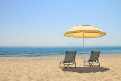 Umbrella and lounge chairs on idyllic beach Stock Photos
