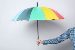 Umbrella in male hand. Colorful umbrella in male hand on grey background Stock Photos
