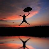 Umbrella man jump. And sunset silhouette Stock Image