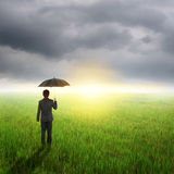 Umbrella man standing to raincloud in grassland with umbrella Stock Image