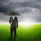 Umbrella man standing to raincloud in grassland with umbrella Stock Photography