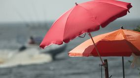 Umbrella and motorboat. On beach shallow depth of field zoom in stock video
