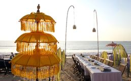 Umbrella in an oceanfront restaurant on the sunset. With table, suspended lights and white tablecloths Royalty Free Stock Images