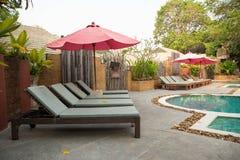 Umbrella pool chair and tropical pool stock photo