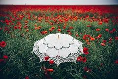 Umbrella in poppies field. Artistic interpretation. Royalty Free Stock Image
