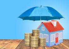 Umbrella protection House coins savings a business. Protection money insurance home concept. Blue umbrella protection House coins savings a business. Protection Royalty Free Stock Photos