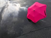 Umbrella and puddle. Umbrella and reflection of the sky in a puddle after a rain Royalty Free Stock Photo