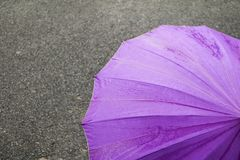 Umbrella purple on road and rain drop with copy space for add text.  Stock Photography