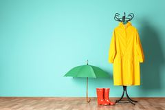 Umbrella, rain coat and boots near color wall. With space for design royalty free stock images