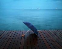 Umbrella in the rain. Umbrella on the platform, at the seaside, rainy day Royalty Free Stock Photos