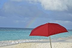 UMbrella and Rainbow on the beach. A red umbrella and an umbrella are silhouetted on the powdery white sand on Shoal Bay of Anguilla Royalty Free Stock Photography