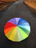 Umbrella Road. A rainbow colored umbrella abandoned on a countryside road wet due to rains Stock Image