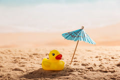 Umbrella and rubber duck in sand against backdrop of coast. Stock Images
