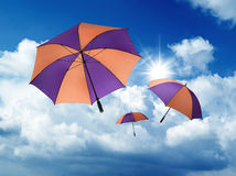 Umbrella's falling from a blue sky Stock Images