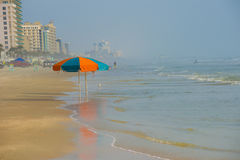 Umbrella in sand hotels. Atlantic ocean in Daytona. empty of people except two red and blue umbrellas standing in the surf. hotels line the beach background Stock Images