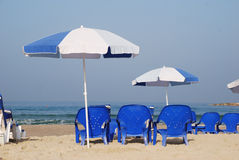 Umbrella in the sand at the seaside. White and Blue umbrella in the sand at the seaside Stock Image