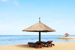 Umbrella on sandy beach. Umbrella and lounge chairs on a sandy beach Royalty Free Stock Photography