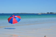 Umbrella by the sea with boat Royalty Free Stock Image