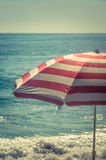 Striped Beach Umbrella With Blue Sea. Umbrella on the Sea Shore Stock Photography