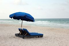 Umbrella shaded beach lounge chairs Stock Photo