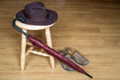 Umbrella, shoes and fedora hat on stool Royalty Free Stock Photography
