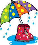 An umbrella and some waterproof boots. A colourful cartoon umbrella and some waterproof boots in a puddle of water, with raindrops splashing down Stock Image