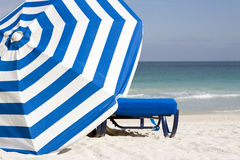 Umbrella and South Beach. Image of blue lounge chair and blue and white striped umbrella set against the South Beach Atlantic shoreline in the late afternoon in stock photo