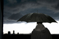 Umbrella-Storm. Man with umbrella in the storm in a winter's evening royalty free stock images